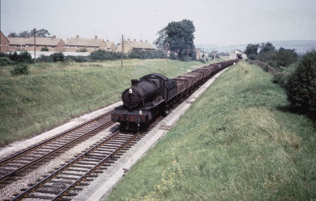 A filthy Manor class 4-6 -0 heading south through the remains of Bishop's Cleeve station with a long train of open wagons